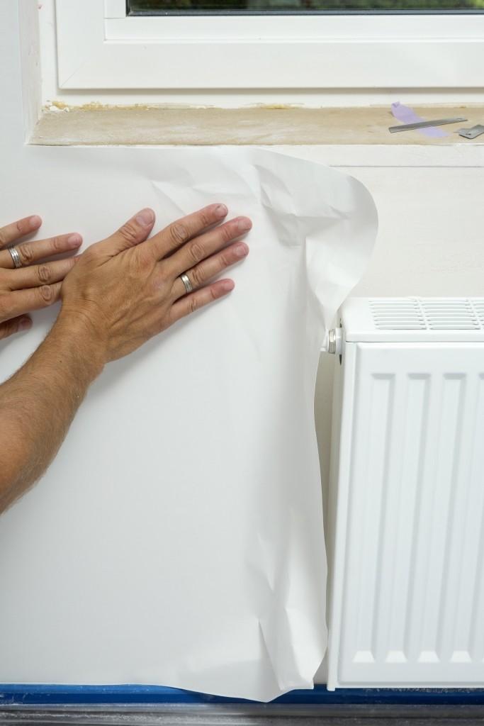 Tapisser avec un papier intissé: les coins et les bords sont à enduire à la brosse