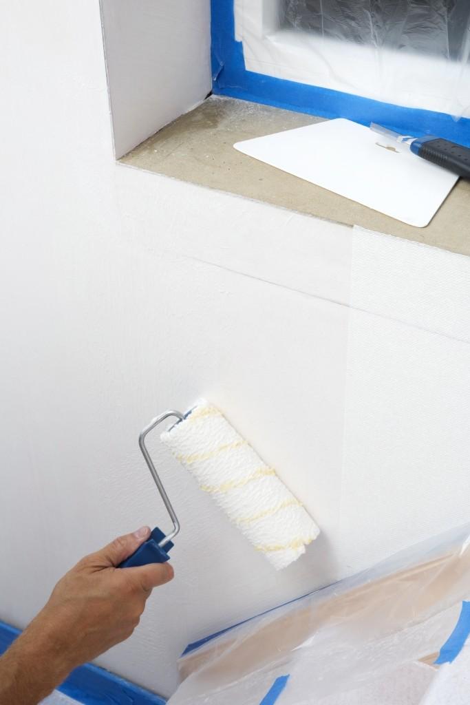 Tapisser avec un papier intissé:  appliquez la colle sur le mur à l'aide d'un rouleau à longues fibres