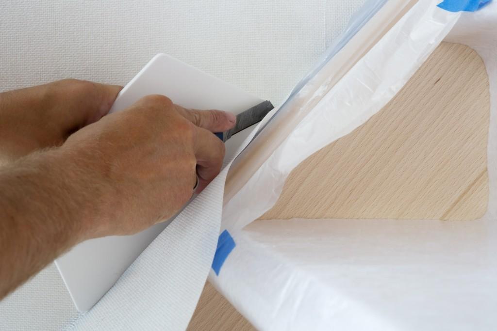 Behangen met vliesbehang: snij het overtollige vlies weg met een scherp cuttermes